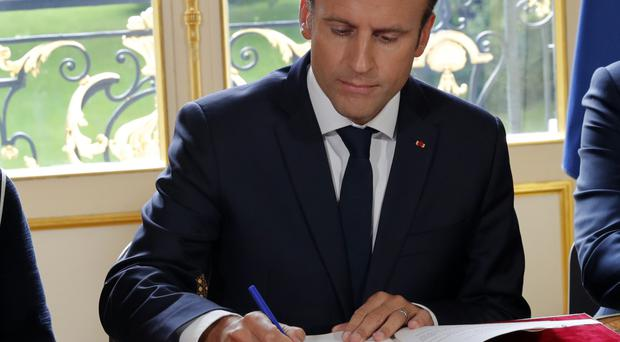 Emmanuel Macron signs documents at the Elysee Palace in Paris (AP)
