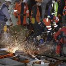 Rescuers try to reach possible survivors trapped inside an office building in the Roma Norte area of Mexico City after the earlier earthquake (AP/Rebecca Blackwell)