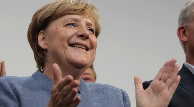 German chancellor Angela Merkel celebrate at the headquarters of the Christian Democratic Union in Berlin (AP)