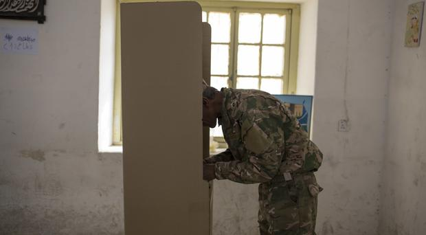 A security guard votes at polling station in the disputed city of Kirkuk (AP)