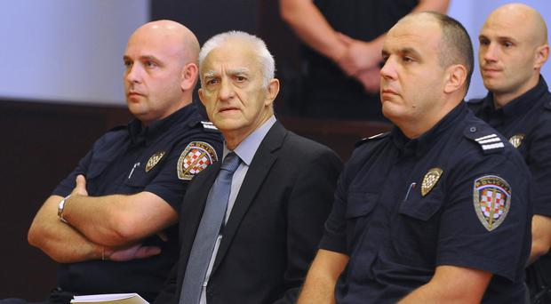 Dragan Vasiljkovic, centre, a former Serb paramilitary commander, sits between guards in a courtroom at the beginning of his trial (AP)