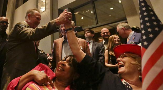 Former Alabama Chief Justice and US Senate candidate Roy Moore, greets supporter Patricia Jones, right, before his election party (AP)