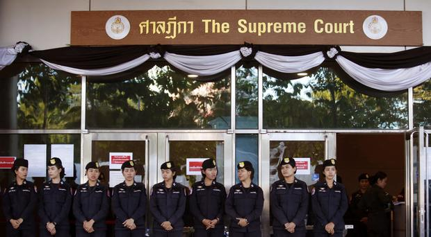 Police officers stand guard outside the Supreme Court in Bangkok, Thailand, where former prime minister Yingluck Shinawatra was sentenced in her absence (AP Photo/Sakchai Lalit)