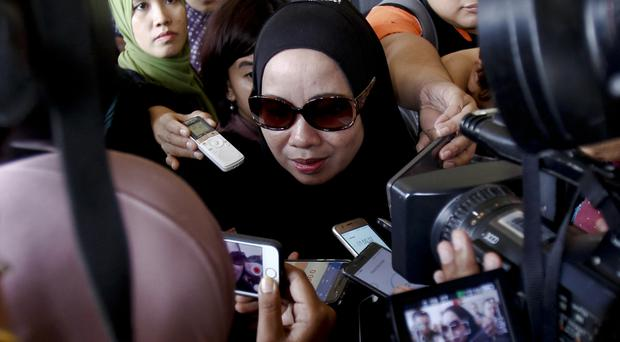 The mother of a victim speaks to journalists outside a court in Kuala Lumpur, Malaysia, where two boys were charged with murder over a fire at an Islamic boarding school (AP Photo/Daniel Chan)