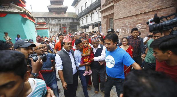 Nepal's new living goddess Trishna Shakya, three, is carried by her father towards a temple palace in Kathmandu (AP)