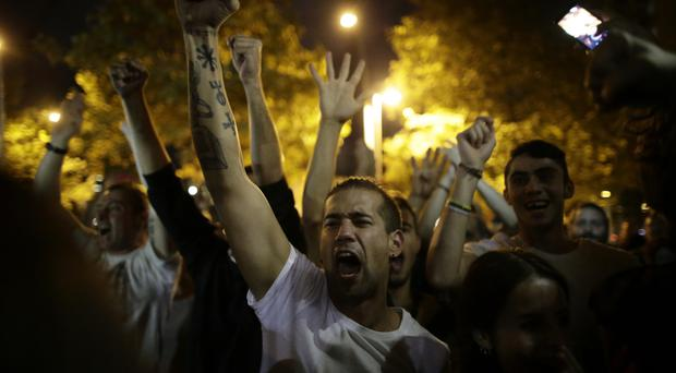 Pro-referendum supporters celebrate on the street after the closing of a polling station (AP Photo/Manu Fernandez)