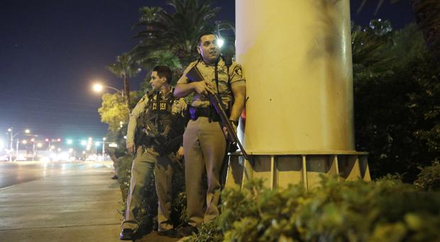 Police officers take cover near the scene of a shooting on the Las Vegas Strip (AP Photo/John Locher)