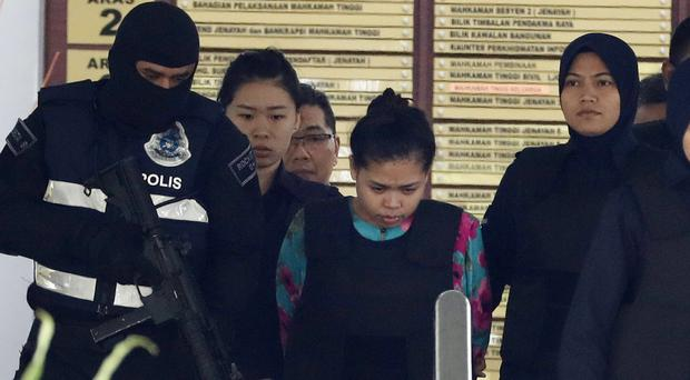 Siti Aisyah of Indonesia, centre, is escorted by police as she leaves the court house (AP)