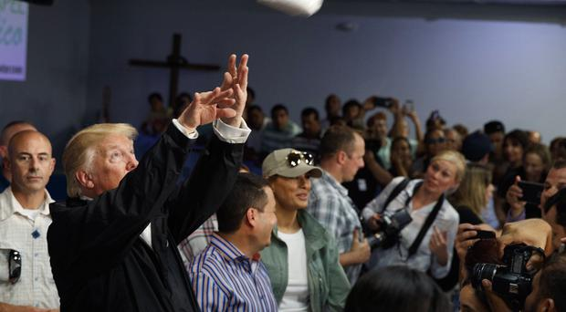 President Donald Trump tosses paper towels into a crowd as he hands out supplies to people affected by Hurricane Maria at Calvary Chapel in Guaynabo, Puerto Rico. (AP Photo/Evan Vucci)