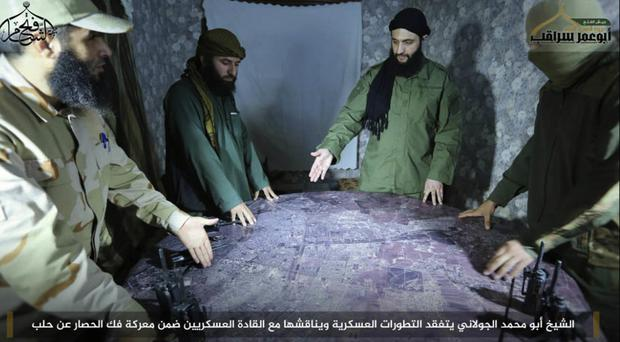 Abu Mohammed al-Golani, second right, is pictured here discussing battlefield details with field commanders over a map, in Aleppo (AP)