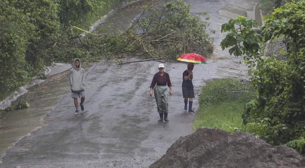 Neighbours walk under the rain past a washed out road in Alajuelita on the outskirts of San Jose, Costa Rica after Tropical Storm Nate (AP)