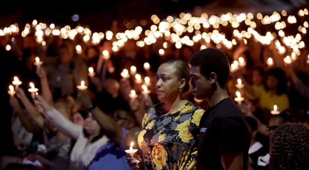 Veronica Hartfield, stands with her son, Ayzayah Hartfield during a candlelight vigil for her husband, Las Vegas police officer Charleston Hartfield, who was killed during the Sunday night shooting at the Route 91 Harvest country music festival. (AP Photo/Gregory Bull)