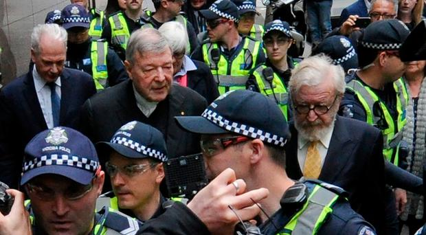 Cardinal Pell (centre left) arriving for yesterday's committal hearing