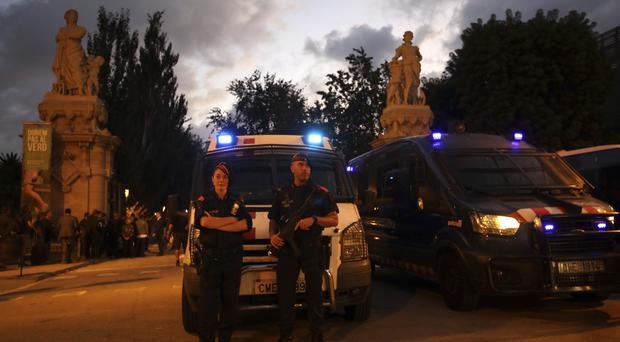Spanish police officers stand guard at the entrance to the Parliament of Catalonia in Barcelona (AP Photo/Emilio Morenatti)