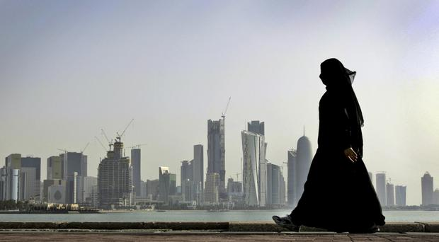 A Qatari woman walks in front of the city skyline in Doha (AP)