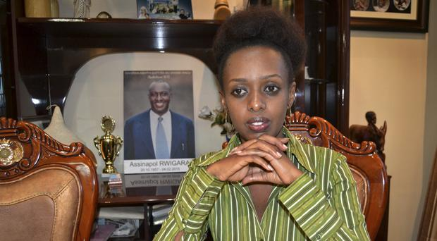 Women's rights activist and presidential candidate Diane Rwigara is photographed next to a portrait of her father, business tycoon Assinapol Rwigara, at her home in Kigali, Rwanda (AP)
