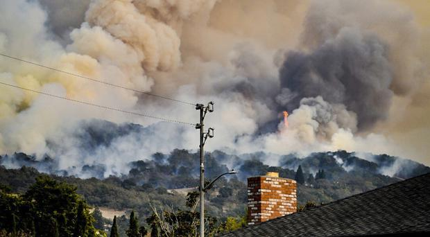 Smoke rises from fires in Santa Rosa, Califiornia, where gusting winds and dry air could drive the next wave of devastating wildfires (Derek Anderson via AP)