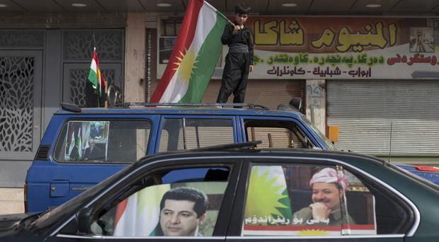 A boy carries a Kurdish flag in Kirkuk, a disputed Iraqi city (AP)