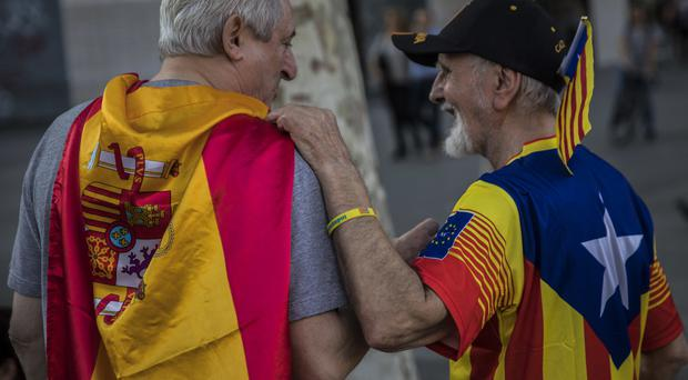 Two men, one wearing a Spanish flag, left, and the other wearing a Catalan estelada, or independence flag, talk in Barcelona (AP)