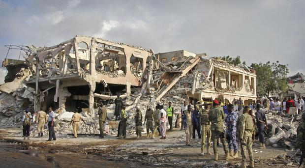 Somali security forces and others gather and search for bodies near destroyed buildings at the scene of Saturday's blast (AP/Farah Abdi Warsameh)