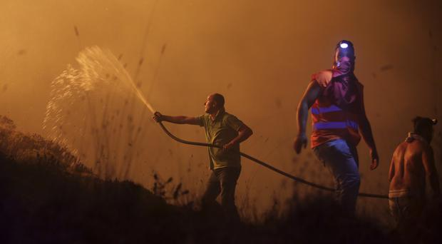 Volunteers use a water hose to fight a wild fire raging near houses in the outskirts of Obidos, Portugal (AP)