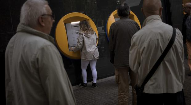 Bank customers wait to withdraw money from a CaixaBank branch in Barcelona (AP Photo/Emilio Morenatti)