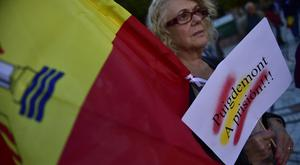 A woman holds a sign reading ''Puigdemont to prison'', referring to Catalonia President Carlos Puigdemont and in support of Spain (AP)