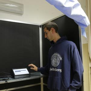 An election worker checks the electronic voting system at the Berchet School polling station in Milan