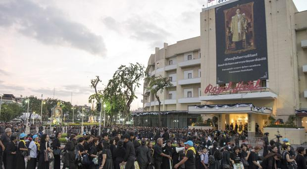 Mourners stand in front of a giant portrait of the late King Bhumibol Adulyadej as they line up for the Royal Cremation ceremony in Bangkok (AP)