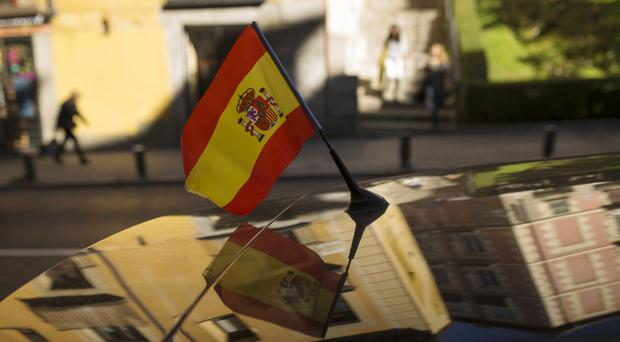 People walk past a car with a Spanish flag attached in Madrid (Francisco Seco/AP)
