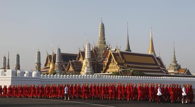 Royal officials walk in front of the Grand Palace during the Royal Funeral in Bangkok, Thailand (AP Photo/Sakchai Lalit)