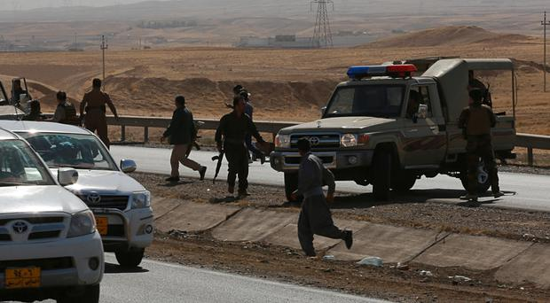Kurdish security forces at a checkpoint in Altun Kupri, on the outskirts of Irbil (AP)