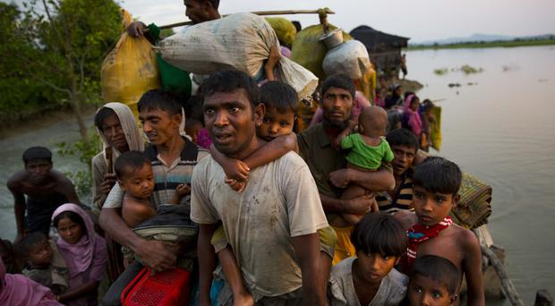 Rohingya Muslims carry their young children and belongings after crossing the border from Myanmar into Bangladesh (AP Photo/Bernat Armangue)