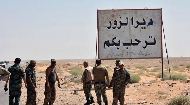 Syrian troops stand next to a sign in Arabic which reads 'Deir el-Zour welcomes you' (Sana via AP, File)