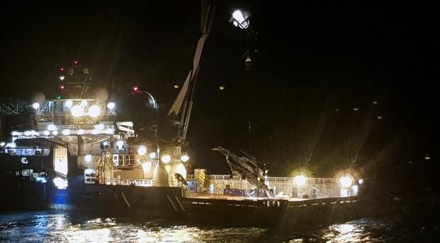 The body, rotor and separated tail of a Russian helicopter which crashed into the sea off Norway is lifted on to the deck of a ship (Accident Investigation Board Norway/Norwegian Police via AP)