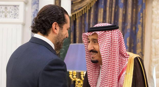 Saudi King Salman, right, shakes hands with outgoing Lebanese prime minister Saad Hariri (AP)