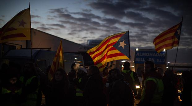 Demonstrators block a highway during a general strike in Borrassa, near Girona (AP)