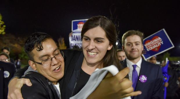 Danica Roem, centre, is greeted by supporters as she prepares to give her victory speech (AP)
