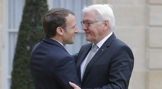French president Emmanuel Macron welcomes German President Frank-Walter Steinmeier at the Elysee Palace in Paris (AP)