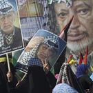 Palestinians wave flags and carry pictures of the late Palestinian president Yasser Arafat in Gaza City (AP)