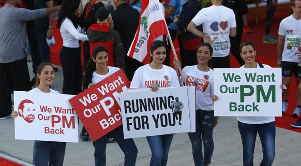 Lebanese women hold placards supporting Saad Hariri during the Beirut Marathon (AP/Hassan Ammar)