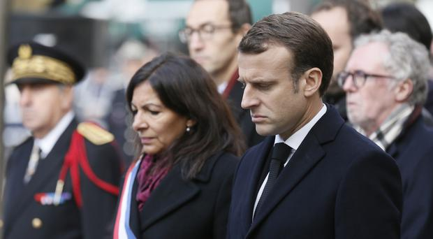 Emmanuel Macron and Paris mayor Anne Hidalgo stand in front of the Comptoir Voltaire bar during a ceremony marking the second anniversary of the Paris attacks (Etienne Laurent, Pool via AP)