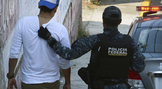 Police detain a man after a shootout with gunmen in central Acapulco (AP)