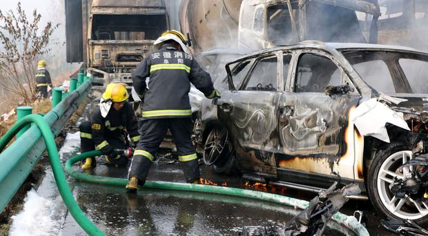 Firefighters work to put out blazes in vehicles after a road accident in Fuyang, China (Chinatopix/AP/PA)