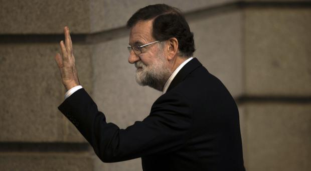 Mariano Rajoy gestures as he arrives at the Spanish parliament for a weekly session in Madrid (Francisco Seco/AP/PA)
