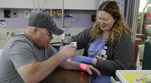 Brian Madeux uses an infrared device to look at his veins as nurse Siobhan Field prepares for the first human gene editing therapy (Eric Risberg/AP/PA)