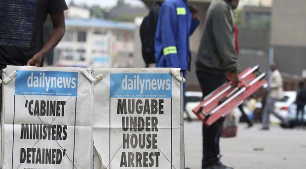 Residents pass a newspaper headline in Harare, Zimbabwe (AP)