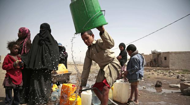 A boy rinses a bucket as he and others collect water from a well on the outskirts of Sanaa, Yemen (Hani Mohammed/AP/PA)