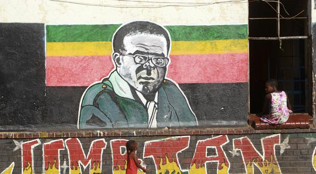 Children play near a painting of Zimbabwean President Robert Mugabe in Harare (AP)