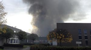 A plume of black smoke rises from the Milcamps waffle factory in Brussels (AP)
